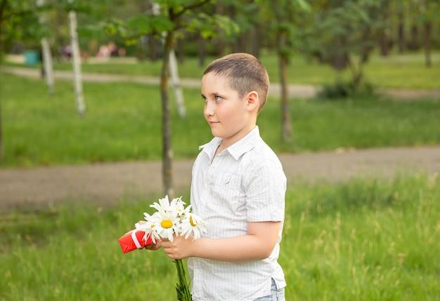 Leuke jongen die verpakte giftdoos met lintboog in wapens houdt.