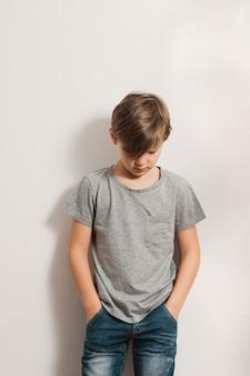 Leuke jongen die zijn hoofd buigt, leunend aan witte muur