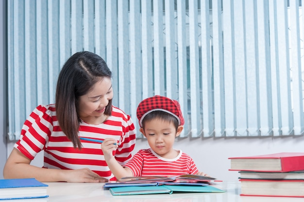 Leuke jongen doet zijn schoolwerk met zijn moeder thuis, hij schrijft op een boek