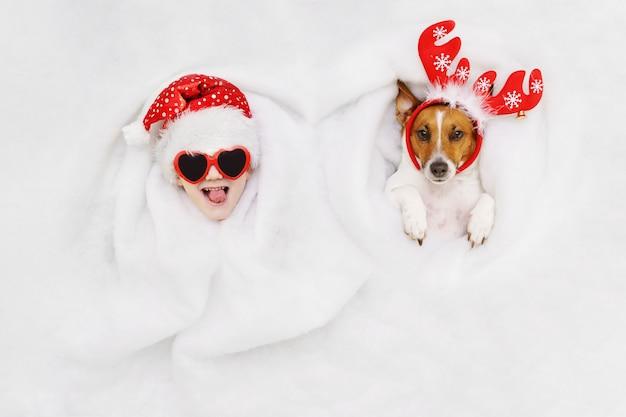 Leuke jongen en hefboom russell hond in een rendier en kerstmanhoed die in sneeuw liggen