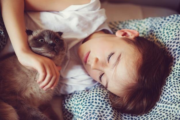 Leuke jongen en kat die 's ochtends in bed liggen. kind en zijn kat thuis. kinderen en huisdieren. mooie jongen met zijn dier. gezellig thuis in de ochtend. de vriendschap van het kind met kat. ochtendhumeur.