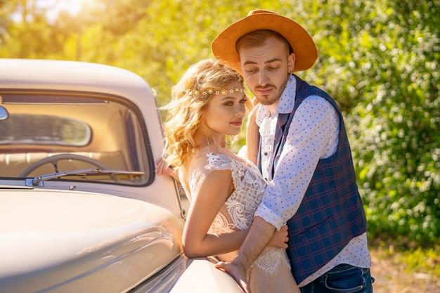 Leuke jongen en meisje in de buurt van een auto op een zonnige dag