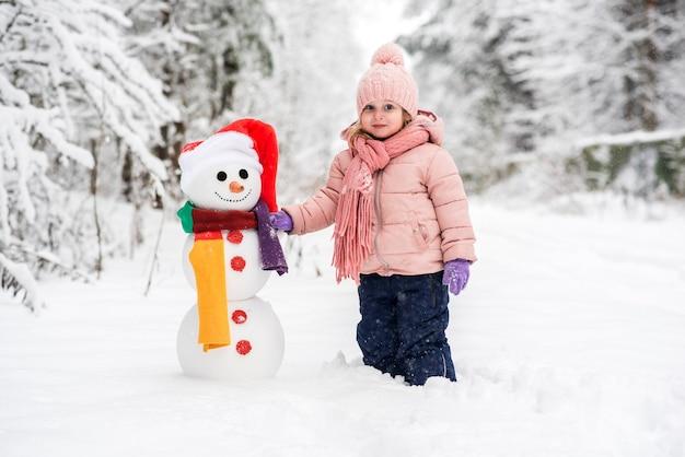 Leuke jongen en meisje sneeuwpop bouwen in wit winter woud