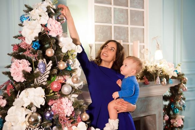 Leuke jongen en zijn moeder die kerstboom verfraaien voor vakantie