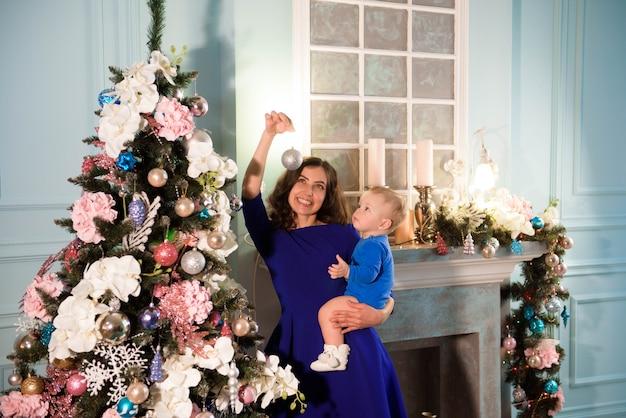 Leuke jongen en zijn moeder die kerstboom versieren voor vakantie