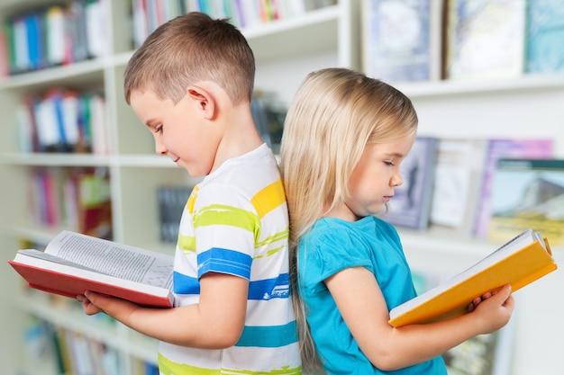 Leuke jongen en zijn zusje met boeken
