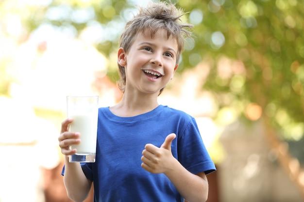 Leuke jongen in blauw shirt met glas melk op wazig