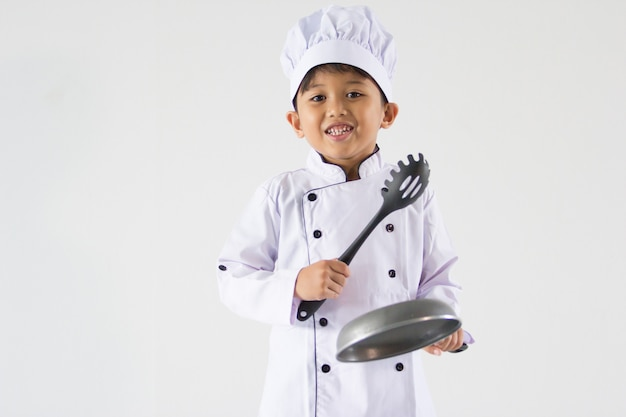 Leuke jongen in chef-kok eenvormig op geïsoleerd wit