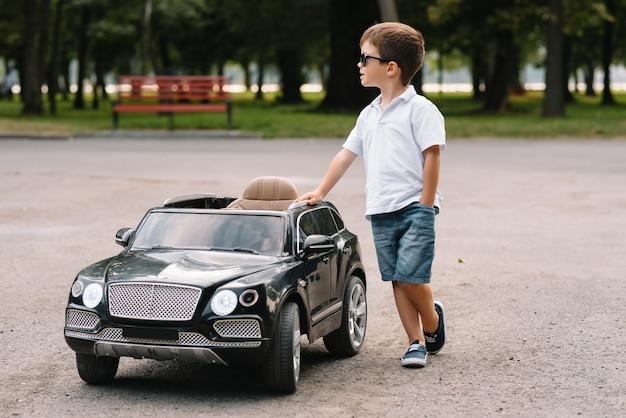 Leuke jongen in het berijden van een zwarte elektrische auto in het park
