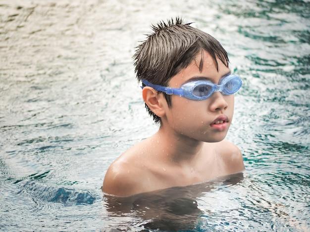 Leuke jongen in het zwembad. gelukkige aziatische jongen in het zwembad.
