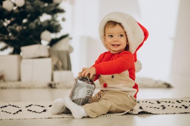 Leuke jongen in kerstmuts openen presenteert op kerstmis