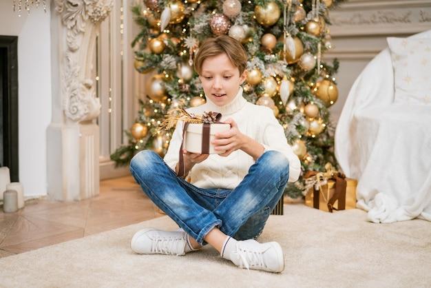 Leuke jongen in trui zit bij de kerstboom met geschenken kaukasische tiener thuis met feestelijke ne...