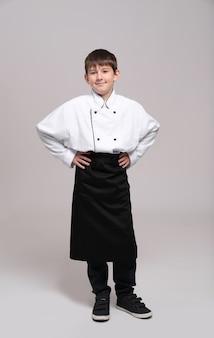 Leuke jongen in uniform chef-kok
