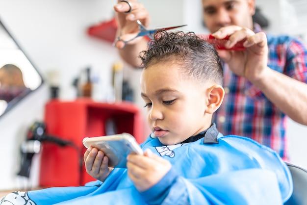 Leuke jongen krijgt een haar knippen in een kapper. schoonheid concept.