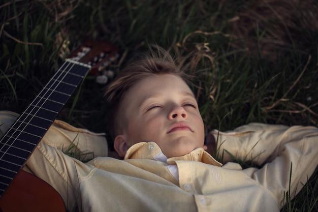 Leuke jongen ligt op het gras met een gitaar op zonsondergang