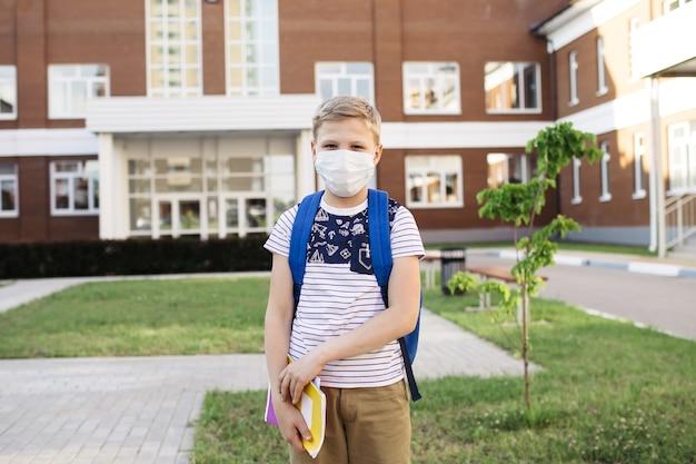 Leuke jongen met een rugzak buiten in masker voor coronaviruspreventie. jongen gaat terug naar school na covid-19 quarantaine en lockdown.