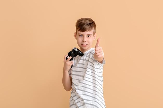 Leuke jongen met gamepad die duim-omhoog toont op kleurenachtergrond