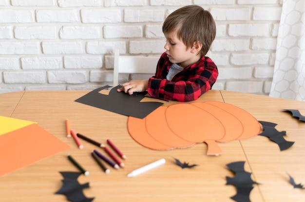 Leuke jongen met halloween-pompoenconcept