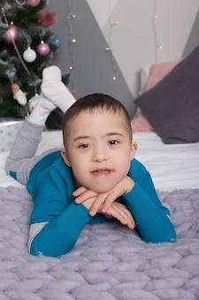 Leuke jongen met het syndroom van down in glazen zitten, glimlachen naar de camera en spelen