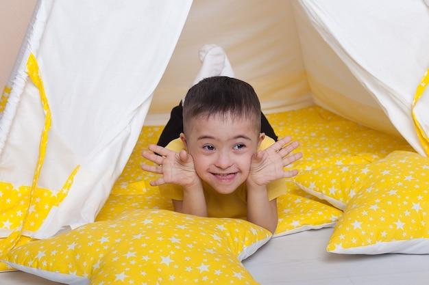 Leuke jongen met het syndroom van down, zittend in een gele hut