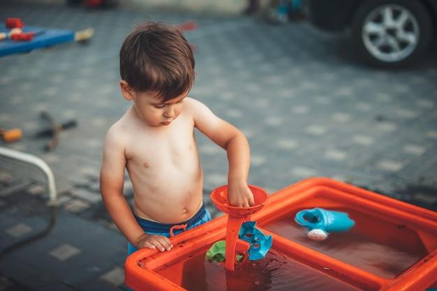 Leuke jongen met ongeklede buik speelt in de tuin met water en plastic speelgoed