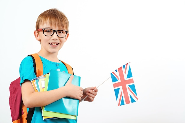 Leuke jongen met rugzak en boeken houdt britse vlag. schoolkind met de vlag van engeland.