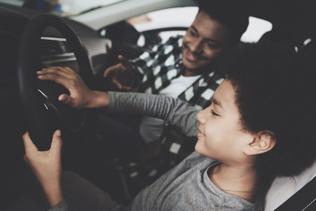 Leuke jongen op stuurwiel papa leert autorijden.