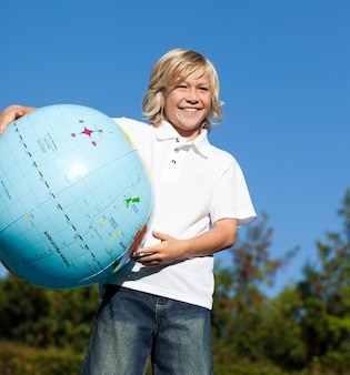 Leuke jongen speelt met een aardse wereld