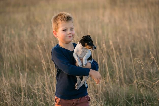 Leuke jongen speelt met zijn hond in de wei