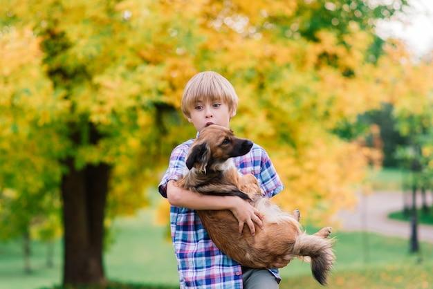 Leuke jongen spelen en wandelen met zijn hond in de wei