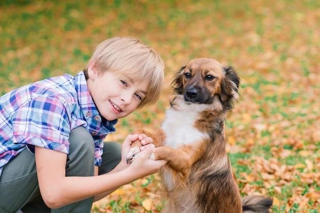 Leuke jongen spelen en wandelen met zijn hond in een weiland.