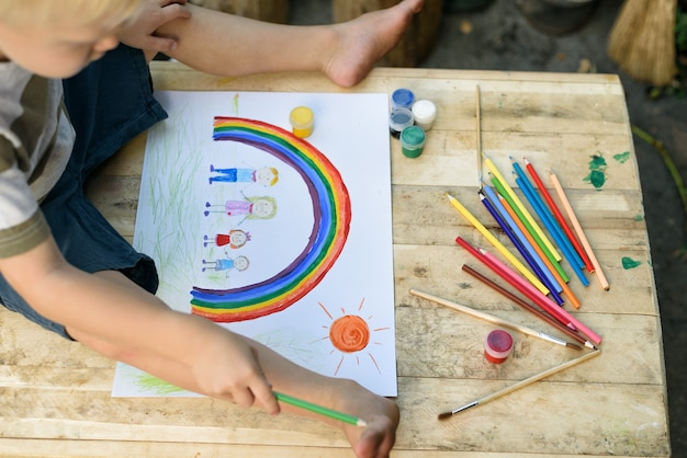 Leuke jongen trekt regenboog en familie