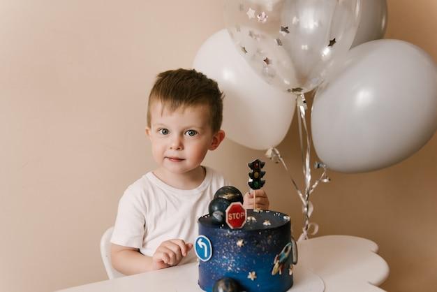 Leuke jongen van 3 jaar viert zijn verjaardag en eet een heerlijke mooie cake, foto van een kind met ballonnen