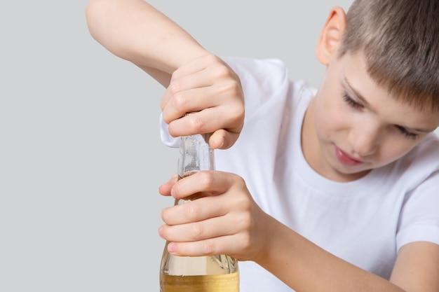 Leuke jongen verdraait een glazen fles soda water, close-up, kopieer ruimte. het concept van verfrissende drankjes, dorstlesser, ongezond eten