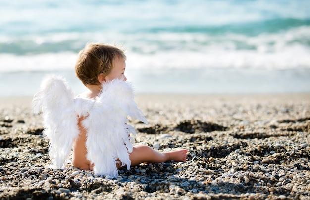 Leuke jongen verkleed als engel zittend op het strand