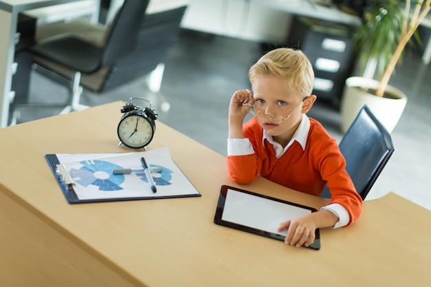 Leuke jongen zit aan het bureau in het kantoor en maakt gebruik van tablet-pc
