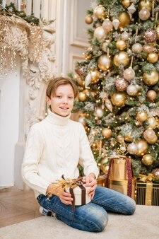Leuke jongen zit bij de kerstboom met geschenken kaukasische tiener in warme gebreide lichte sweater...
