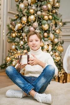 Leuke jongen zit bij de kerstboom met geschenken kaukasische tiener in warme gebreide lichte trui si...