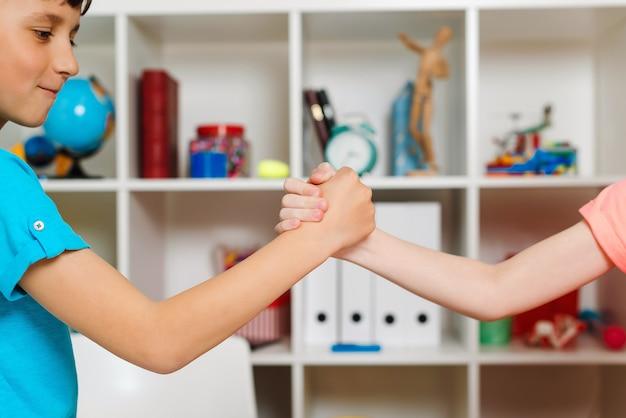 Leuke jongens die handen schudden en elkaars hand vangen.