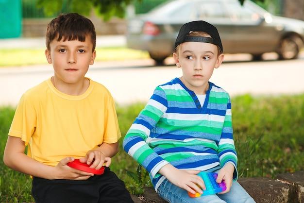 Leuke jongens spelen met trendy pop it-speelgoed. vrienden op een wandeling met siliconen bubbelspeelgoed. jongens die buiten plezier hebben. modern antistress speelgoed voor kinderen. mode, lifestyle en vrije tijd voor kinderen.
