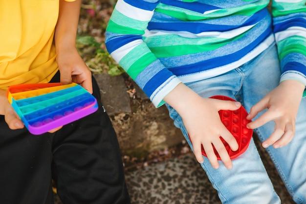 Leuke jongens spelen met trendy pop it-speelgoed. vrienden op een wandeling met siliconen bubbelspeelgoed.