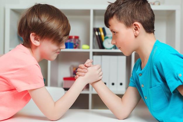 Leuke jongens strijden in armworstelen tijdens de pauze. gelukkige vrienden die armworstelen spelen terwijl ze naar elkaar kijken. leuke broers die tijd samen thuis doorbrengen.