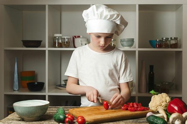 Leuke jongenschef-kok die groenten snijdt voor salade kinderchef-kok in de keuken jongen die chef-kokuniform draagt