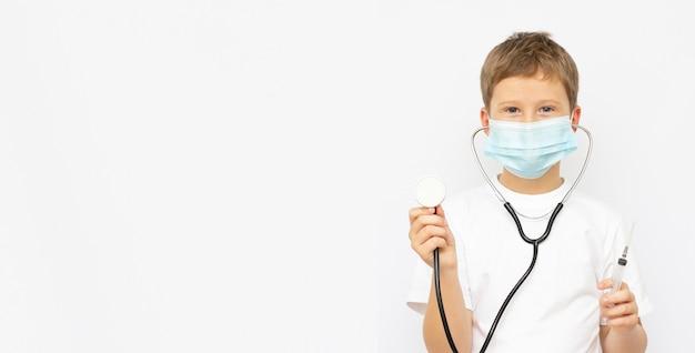 Leuke jongensdokter die medisch masker draagt en duimen opgeeft die op lichtblauwe achtergrond worden geïsoleerd