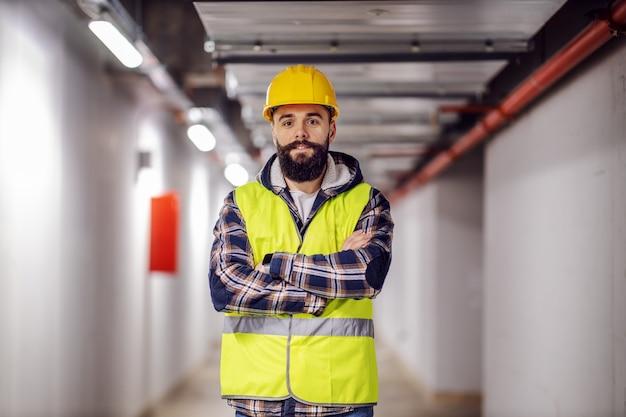 Leuke kaukasische bebaarde bouwvakker met veiligheidshelm op hoofd in vest staande met gekruiste armen op de bouwplaats