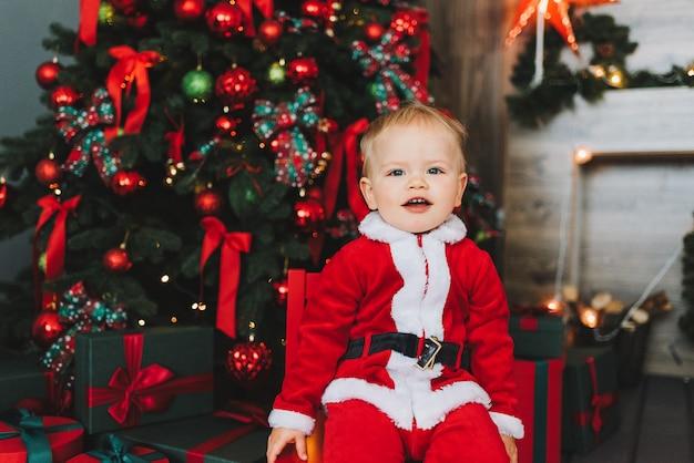 Leuke kaukasische kleine peuterjongen die kerstmankostuum draagt onder kerstboom