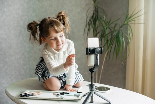 Leuke kaukasische videovlogger van het babymeisje, telefoon op een statief.