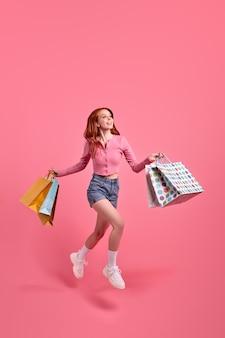 Leuke kaukasische vrouw vrijetijdskleding haast zich na het winkelen met pakketten met aankoop in handen mensen lifestyle concept mock up kopie ruimte geïsoleerde roze achtergrond in studio