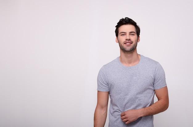 Leuke kerel die camera bekijkt en zijn t-shirt aanpast, die zich op een wit bevindt.