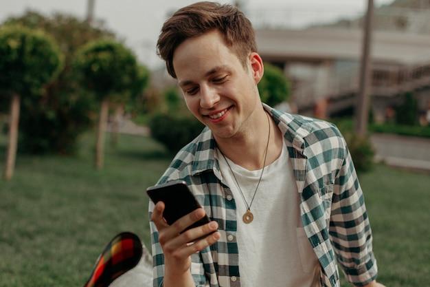 Leuke kerel die mobiele zitting op gras bekijkt